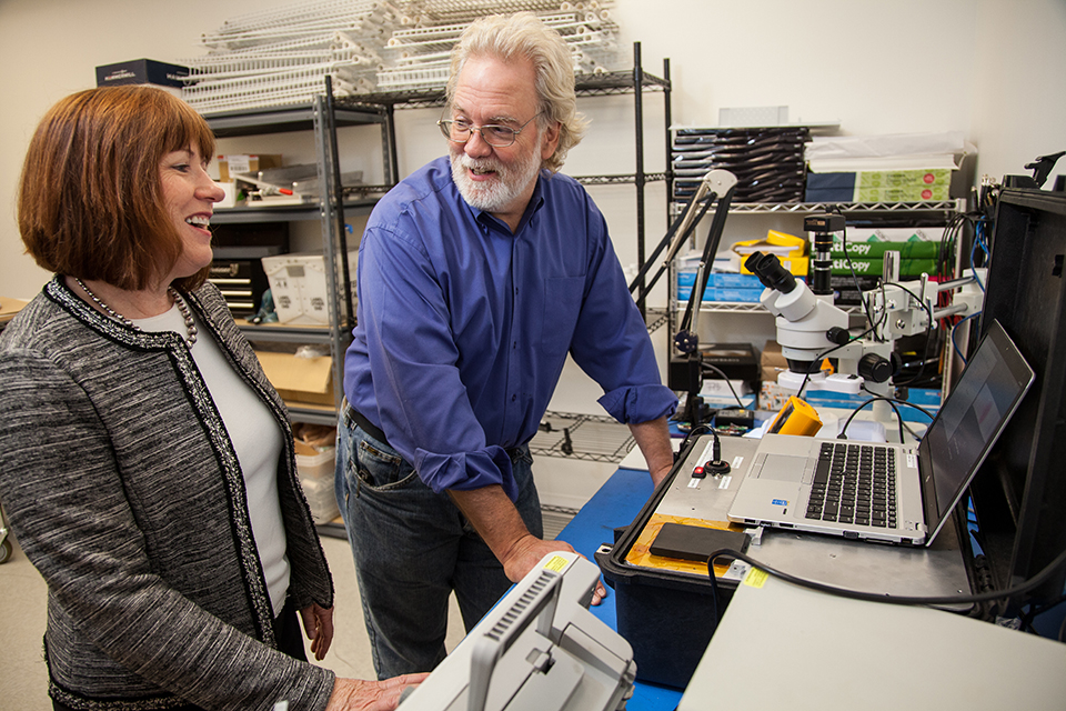 Patti White, CEO of Hemex Health, speaks with Martin Rockwell, electrical engineering manager at Andrew Cooper, about a prototype of the diagnostic equipment designed to test for sickle cell disease and malaria in a quick and inexpensive way. Photo © Tim LaBarge 2016