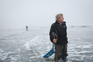 Northwest Wild Products owner Ron Neva pauses while searching for razor clams