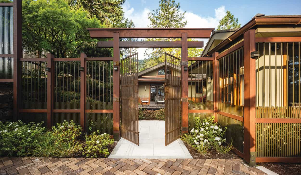 This modern home in Ashland has a gate and fence inspired by a Japanese screen. Constructed of wood and powder-coated steel, it was built without nails, screws or glue.