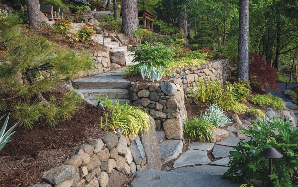 The earth-toned stones on terraced slopes switch back down the backyard onto a bluestone patio.