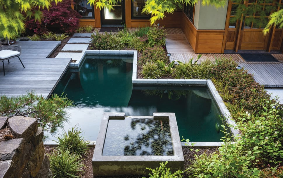 Water falls from a limestone outcropping into a 5,000-gallon koi pond where fish can flaunt their vibrant colors in the deep blue or find niches in which to hide.